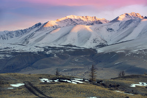 Snowy mountain valley at sunrise