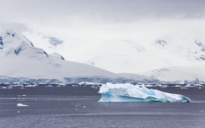 Snowy, rocky coast and iceberg under a cloudy sky