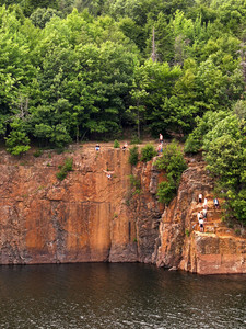 Some crazy kids cliff jumping off the side of a mountain from 60 feet up into the water below.