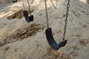 Some empty playground swings at the park.