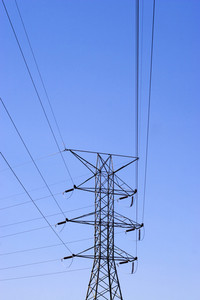 Some high power lines over a bright blue sky.