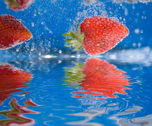 Some juicy red strawberries plunging into some water with reflections.