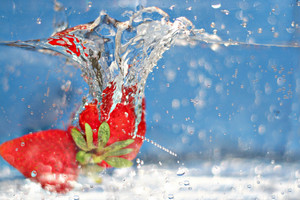 Some ripe and juicy red strawberries plunging into some water.  Shallow depth of field.