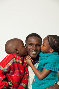 Son and daughter kissing her father