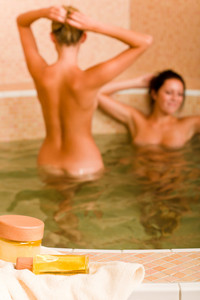 Spa and beauty products two naked women inside pool water beauty health