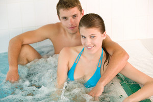 Spa - young loving couple enjoy romantic hot tub