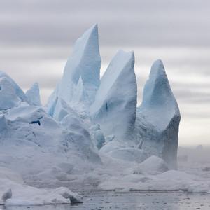 Spiky peaks of an iceberg against a cloudy sky