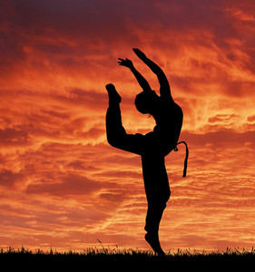 Sport acrobatic girl against fantastic red sky