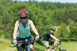 Sport mountain biking happy couple riding uphill in sunny countryside