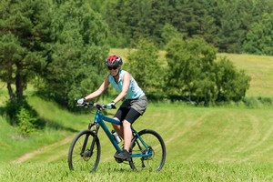 Sport mountain biking happy girl riding uphill in sunny countryside