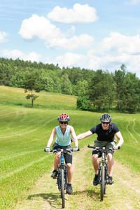 Sport mountain biking - man pushing young girl uphill sunny countryside