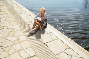 Sport woman relax on pier by lake marina summer day