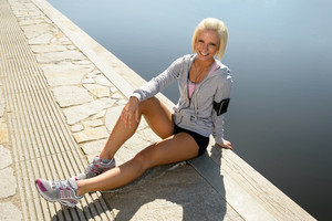 Sport woman relax on pier sitting by bay sunny day