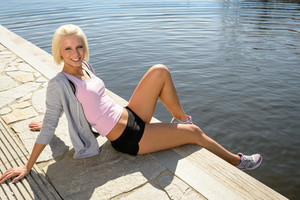 Sport woman summer relax sitting by water pier