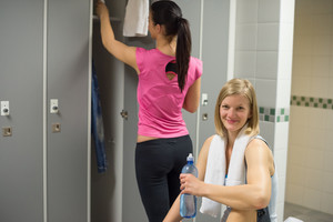Sport woman with friend in background at gym's locker room