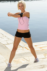 Sport young woman stretch body by pier marina sunny day