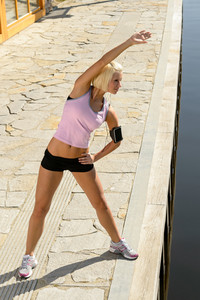 Sport young woman stretch body by water pier summer day