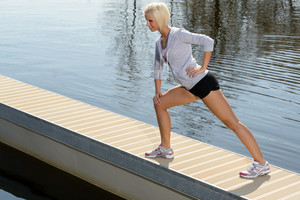 Sport young woman stretch body on lake pier sunny day