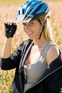 Sportive biking young attractive woman wearing helmet portrait sunny countryside