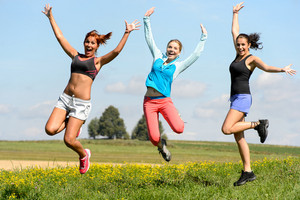 Sportive friends jumping cheerful on sunny meadow teenage girls