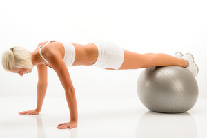 Sportive woman doing pushup exercise on fitness ball white background