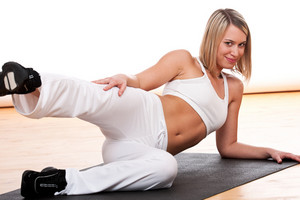 Sportive woman exercising on black mat