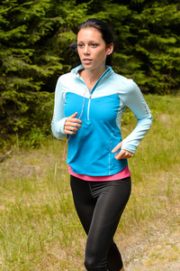 Sportive woman running  through meadow in countryside close-up