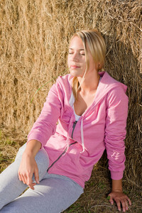 Sportive young woman relax lean against hay bales sunset countryside
