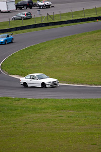 Sports car racing around a road course at intense speeds.
