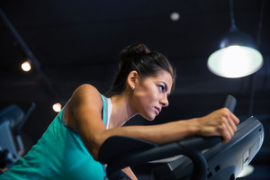 Sports woman workout on exercises machine in fitness gym