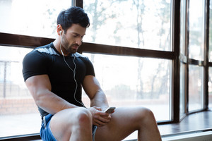 Sportsman wearing blue shorts and black t-shirt listenin to music