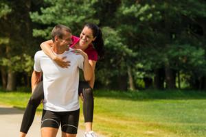 Sporty boyfriend giving piggyback ride to his girlfriend