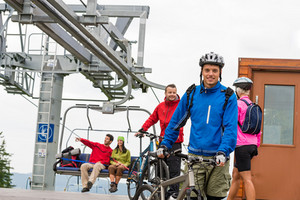 Sporty couple getting on bicycles after chair lift trip