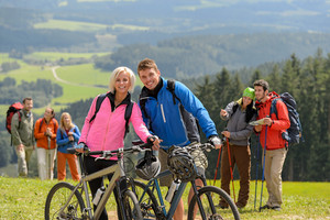 Sporty cyclist couple and hikers posing during springtime weekend