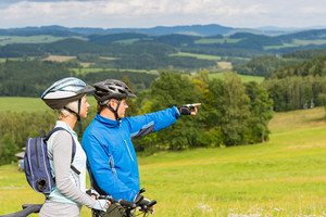 Sporty cyclist couple,man pointing to beautiful landscape