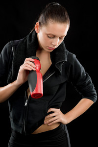 Sporty woman standing with towel and bottle on black background