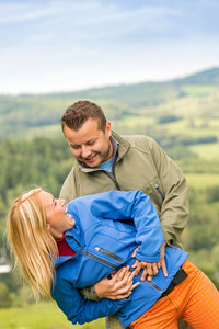 Sporty young couple hugging in front of scenic landscape