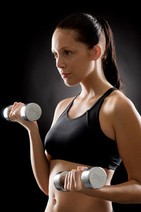 Sporty young woman holding dumbbells on black background