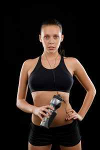 Sporty young woman posing with headphones and bottle black background