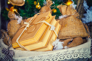 Stack of books and other presents in basket. Christmas decoration