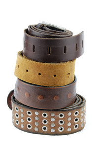 Stack Pile Of Leather Belts On White