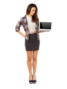 Standing woman in the studio holding a laptop showing an empty screen