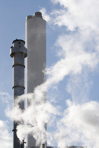 Steel smoke stacks atop buildings billowing with steam and smoke.