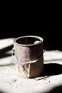 Still life shot of a rusty old paint bucket under dramatic lighting.