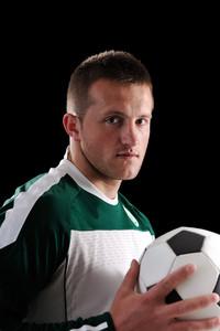 Stock image of man holding soccer ball over dark background