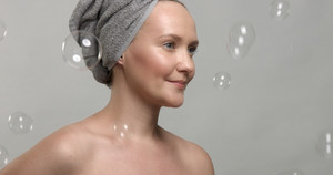30's woman wears a towel after bath surrounded by soap bubbles looking at camera Slow motion footage