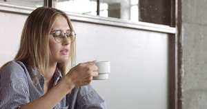 A blond pretty model in an office decorated with concrete and metal puts down her smartphone, sighs and drinks some coffee