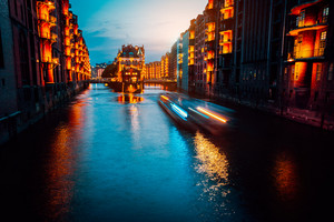 A colorfully illuminated boat cruising on the Wandrahmsfleet at night. The Warehouse District in Hamburg, Germany. The district is located within the HafenCity quarter. Long exposure
