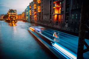A colorfully illuminated boat cruising on the Wandrahmsfleet at night. The Warehouse District in Hamburg, Germany. The district located within the HafenCity quarter. Long exposure