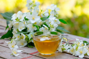 A cup of green tea with jasmine flowers on grunge wooden table outdoors